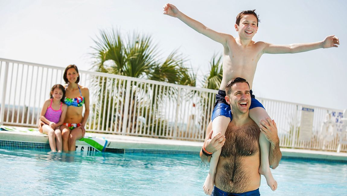 Son on his fathers shoulders in the pool