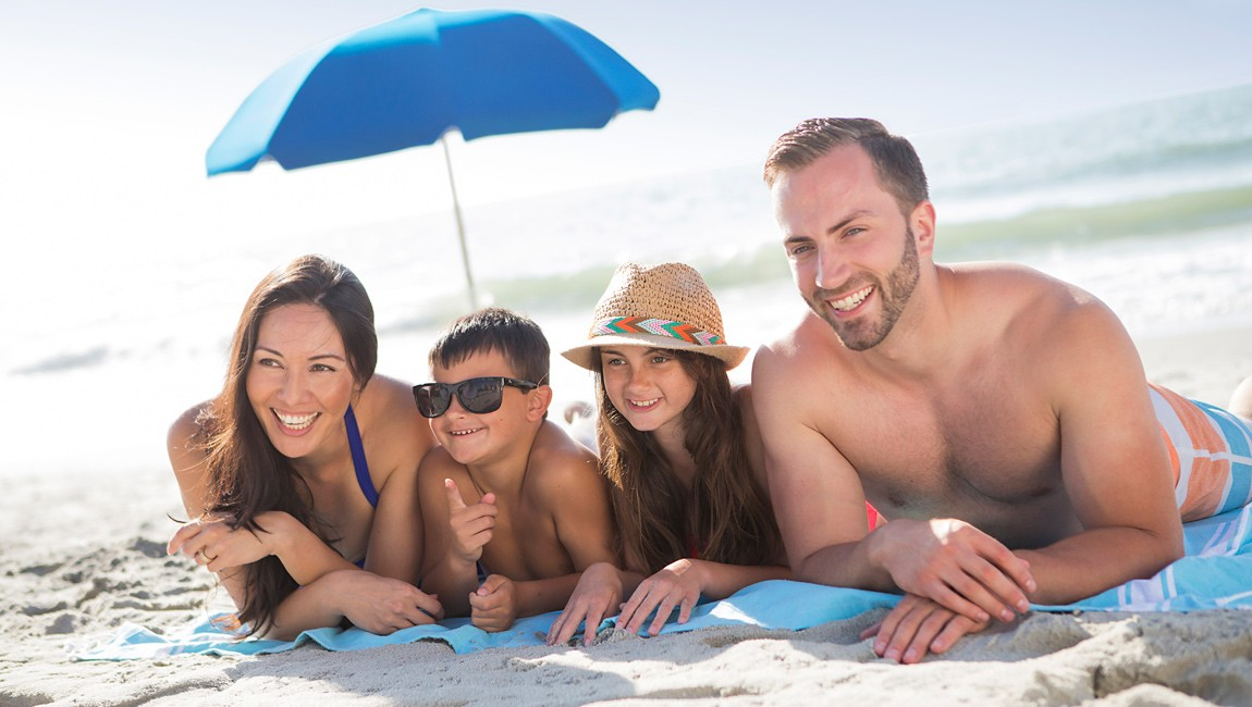 family with an umbrella on the beach