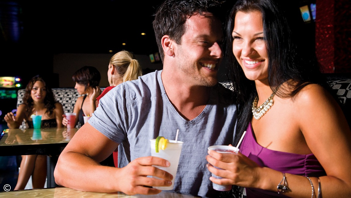 couple enjoying drinks at bowling alley