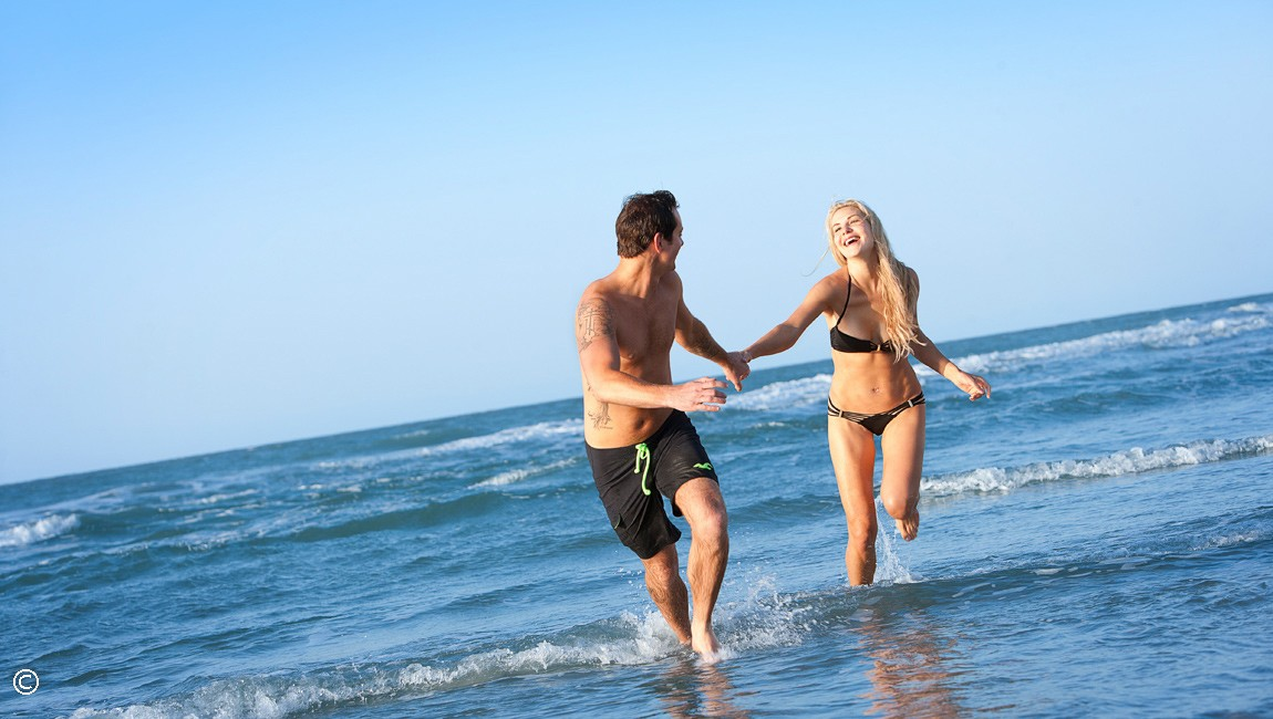 couple running on beach at hotel blue